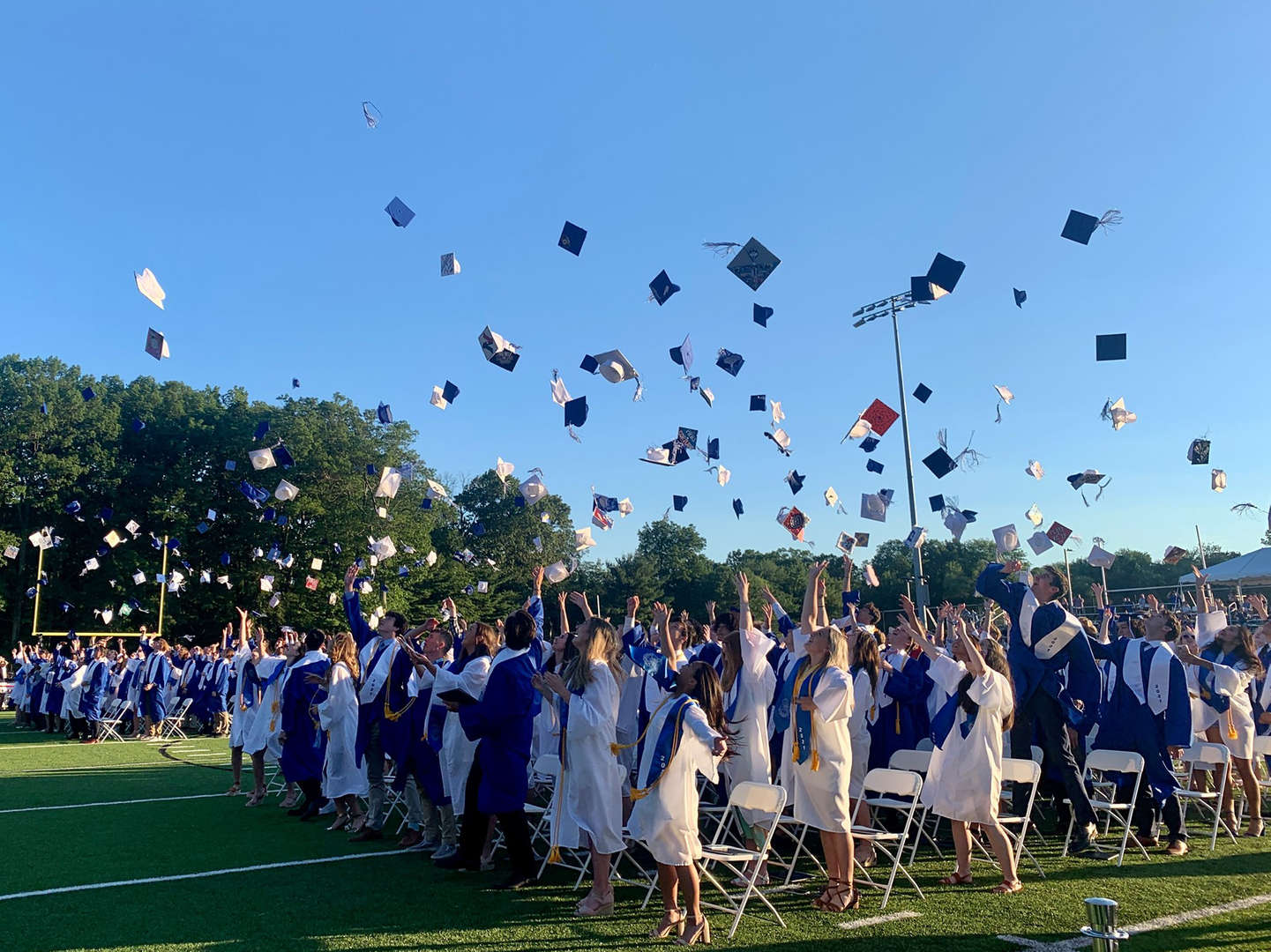 The graduating class tosses their caps into the air as they graduate