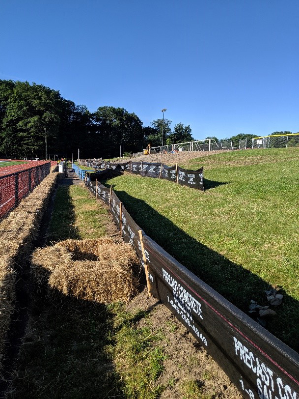 Soil erosion silt fences and hay bales placed on site in advance of foundation work for bleachers & concessions building.