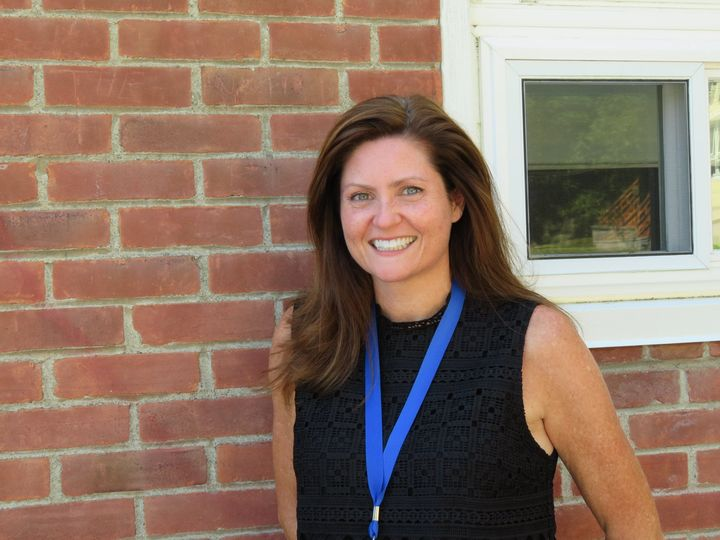 New school principal poses in front of building