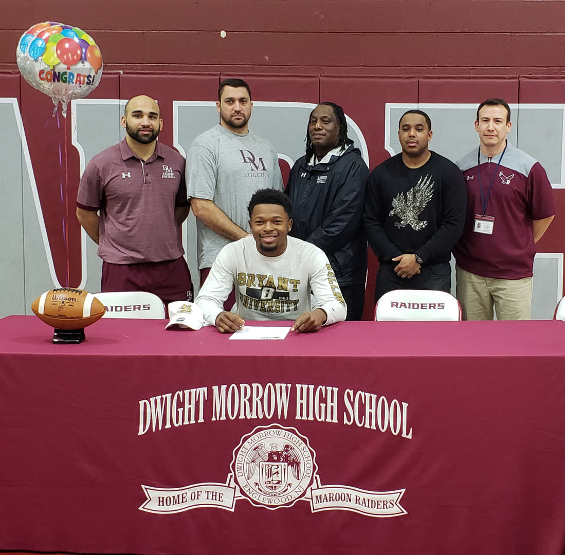 Jihad Edmond signing the commitment letter to play football at Bryant University