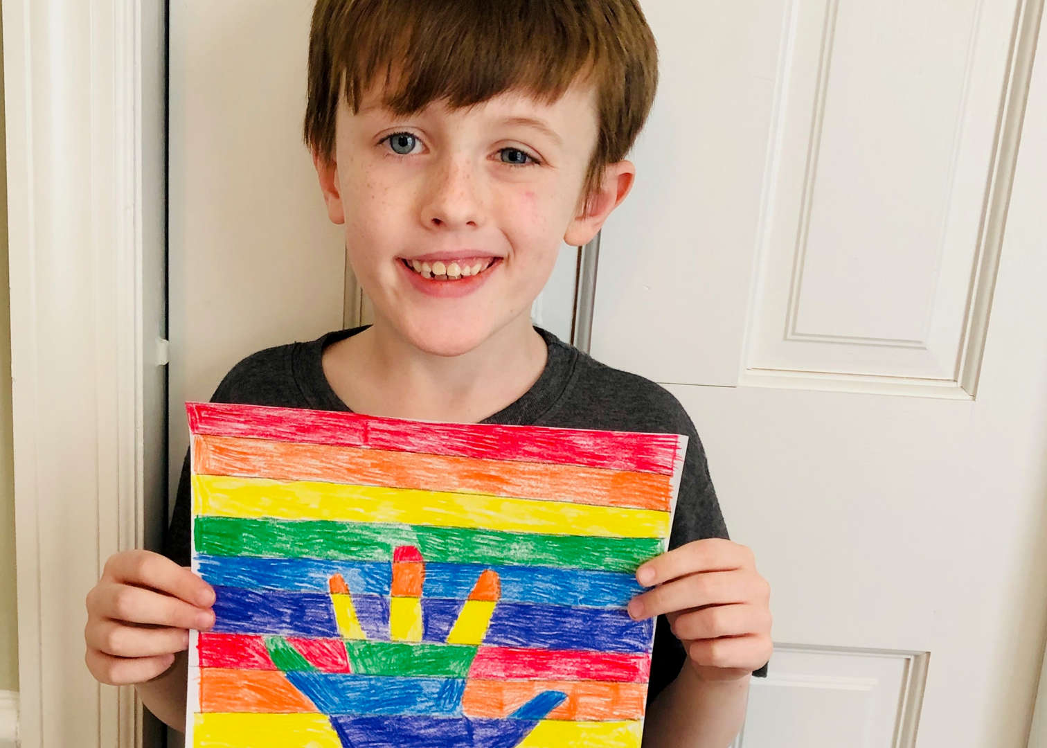 Male student with rainbow hand artwork