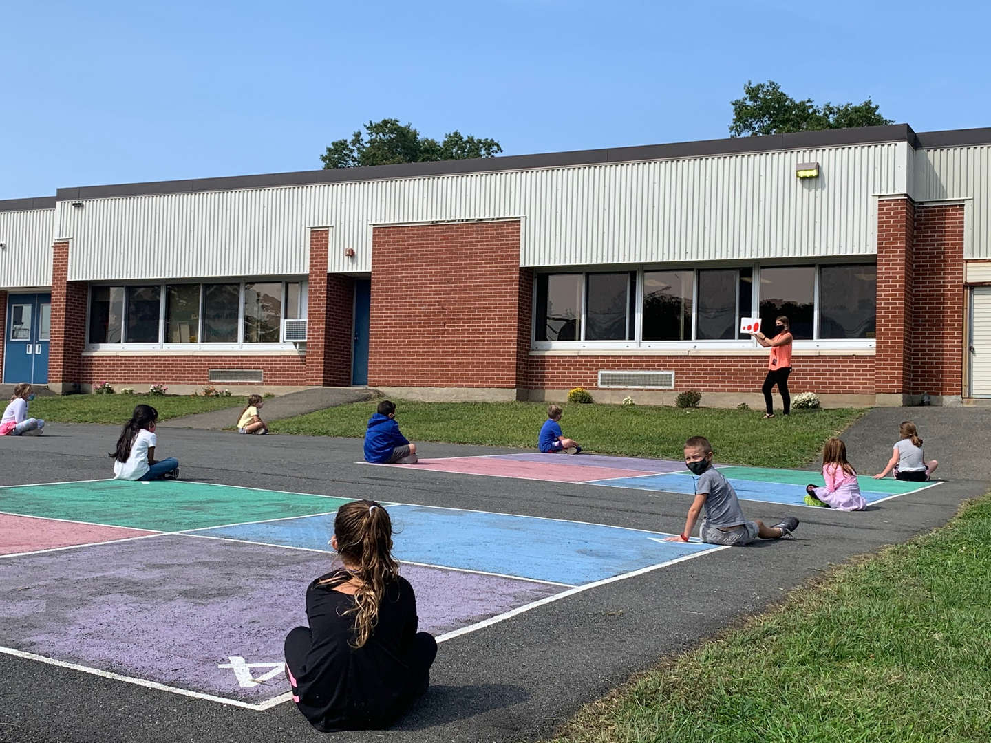 Teacher reading to students on blacktop