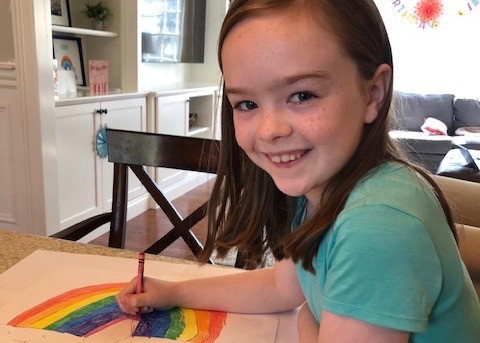 Student drawing a rainbow