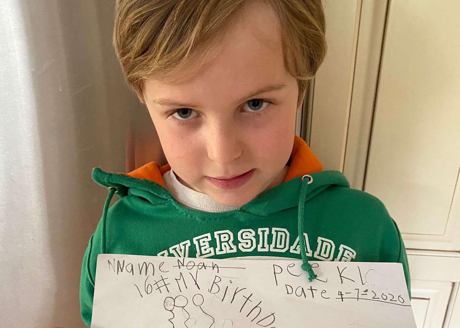 Boy showing work on birthday board
