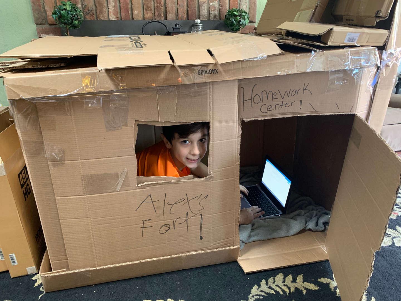 Student inside cardboard fort