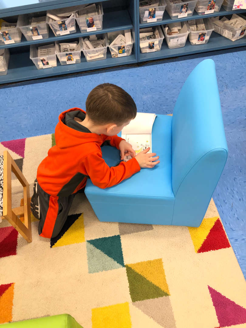 Student reading at a chair