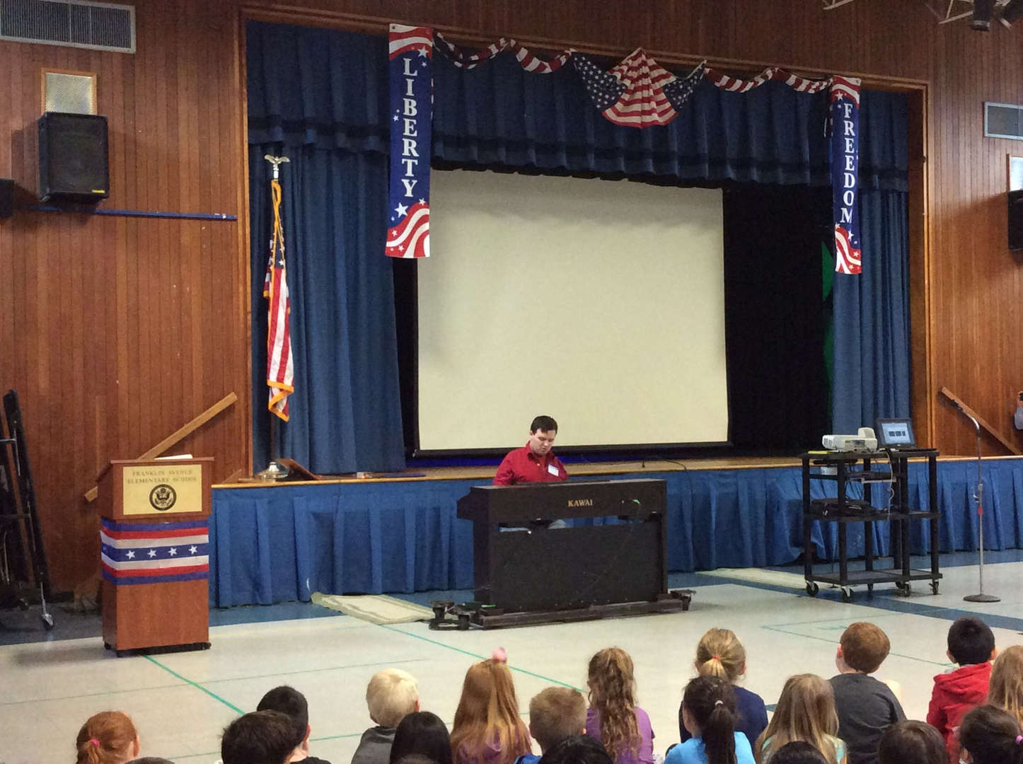 Young man playing piano for students.