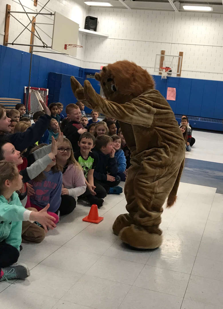 Roary high-fiving at the PBIS Assembly on Teamwork!