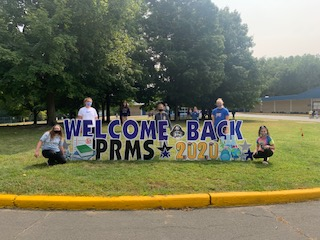 Students around Welcome back sign
