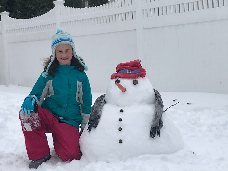kneeling next to a snowman
