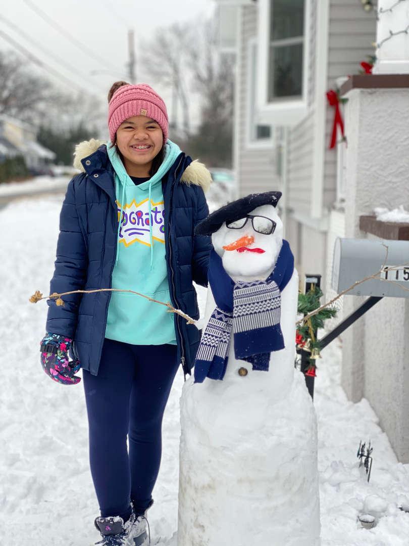 Standing next to a snowman