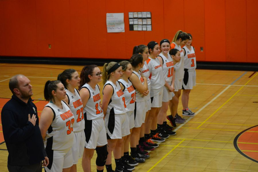 Girl's Varsity Basketball Team Standing for the Anthem