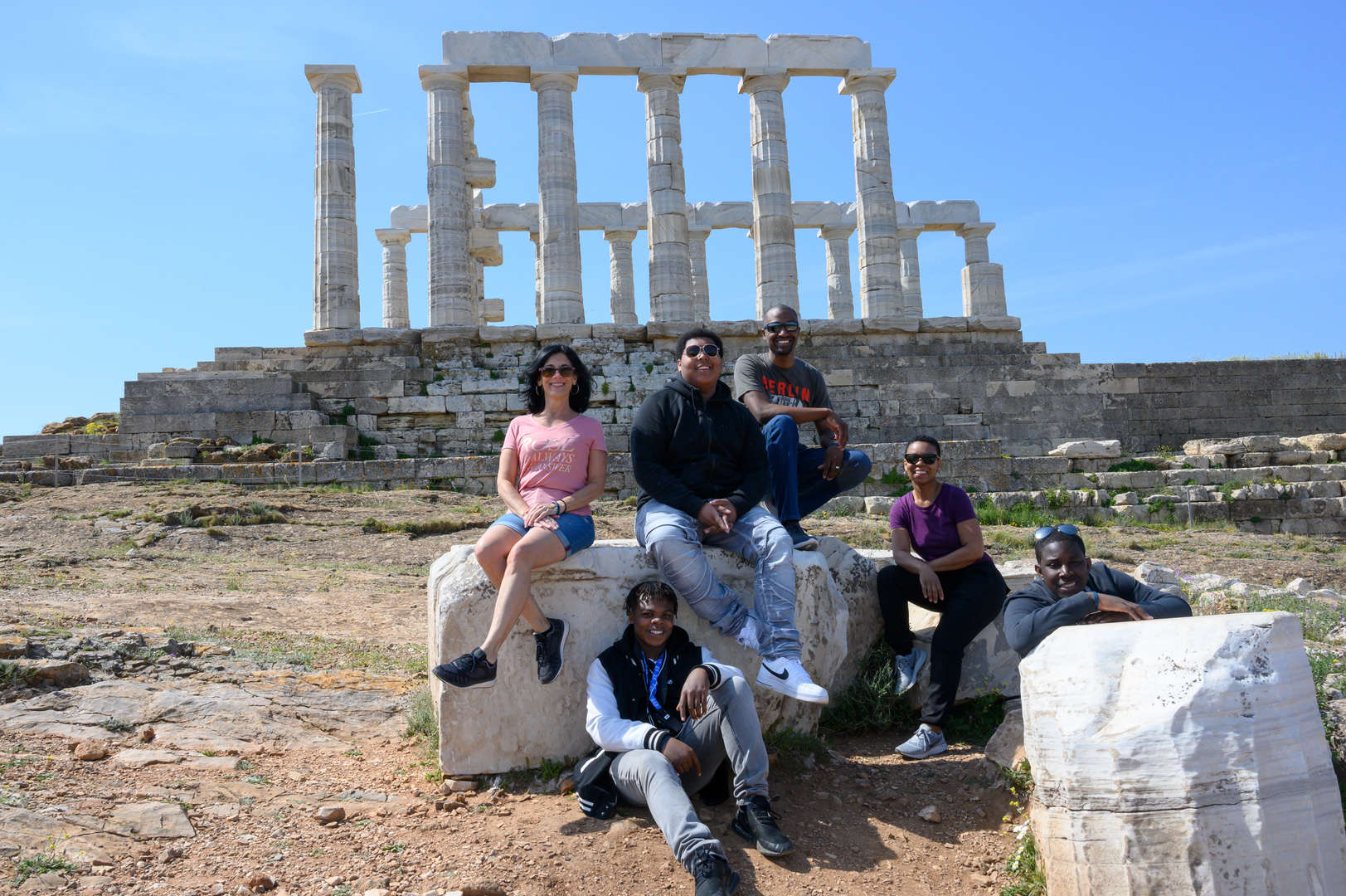 Participants posing in front of an ancient temple while on a trip to Greece