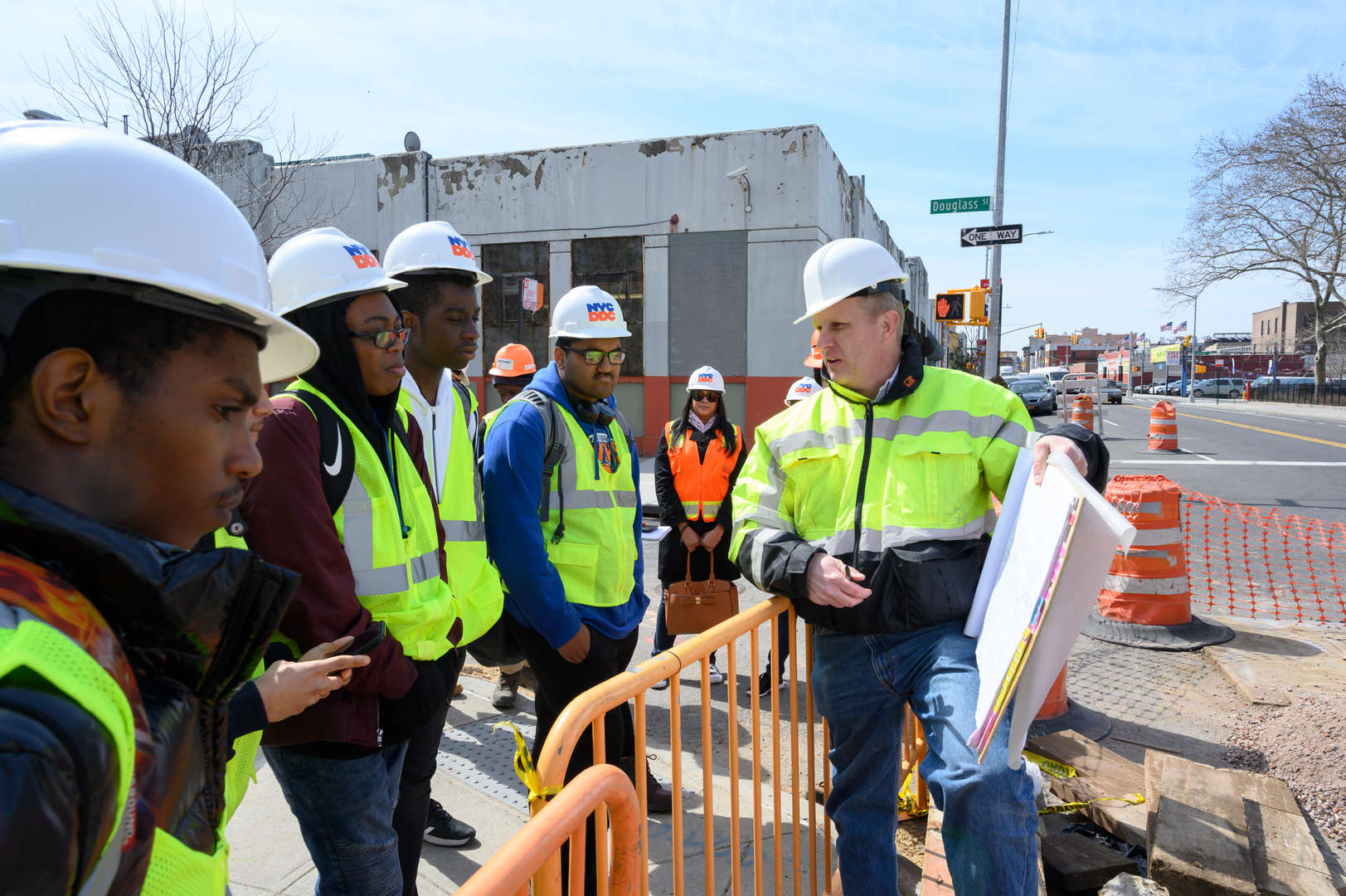 Construction supervisor explaining a work schedule to students