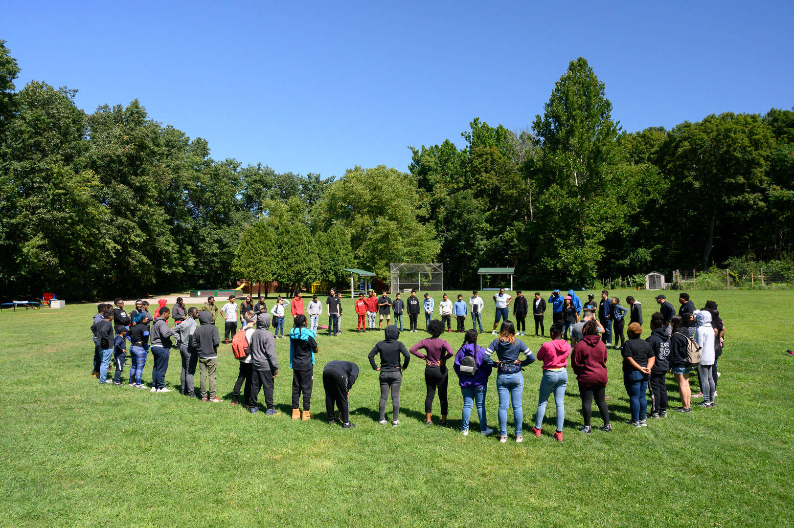 A large group of students standing in a circle on a field with trees in the background