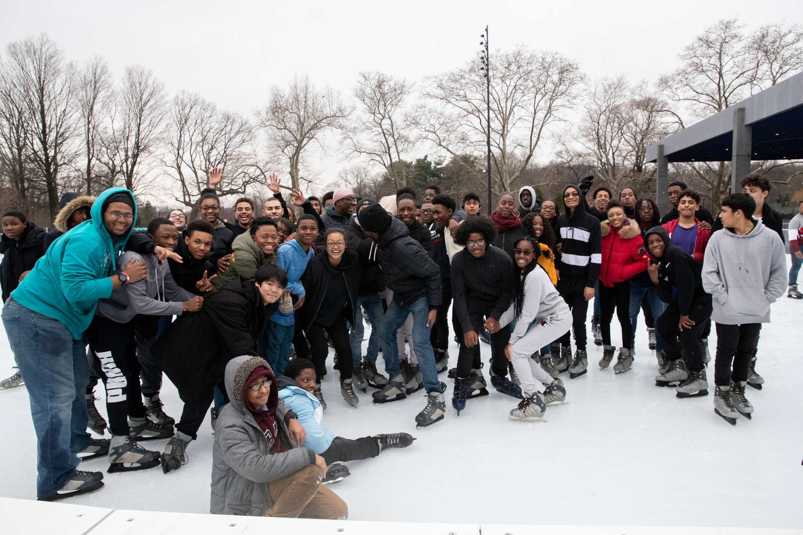 Students gathering for a group photo at the ice skating rink