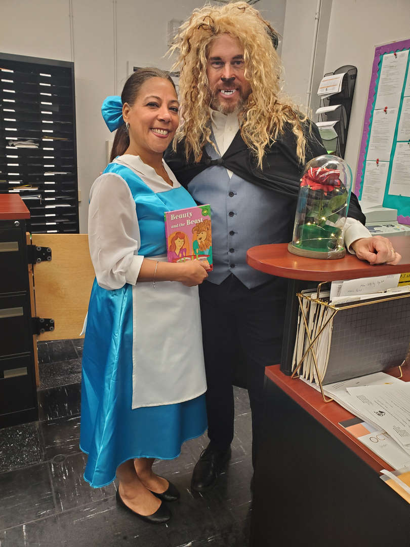 Principal's secretary and assistant principal dressed up as Belle and Beast from Beauty and the Beast.