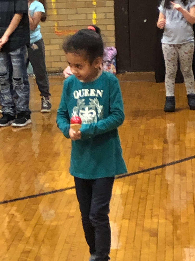 A student in a green shirt racing in an egg race.