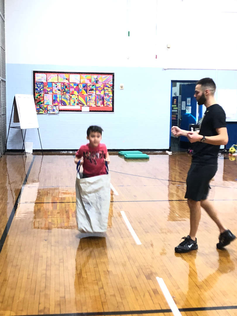 A teacher cheering on a student in a potato sack.