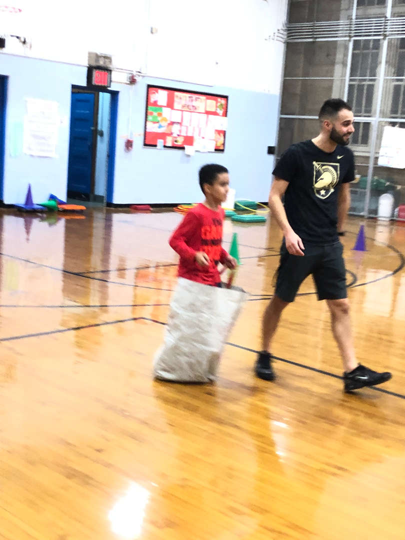 A teacher accompanying a student in a potato sack.