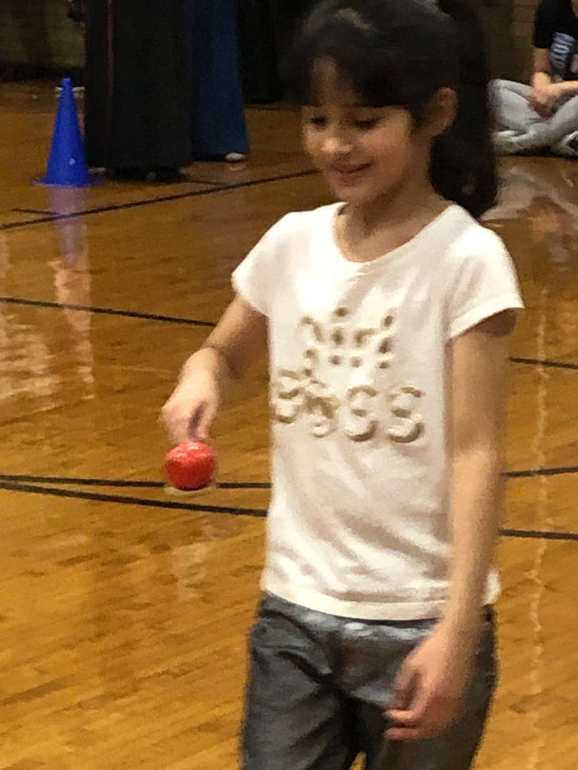 Another student racing in an egg race with a red egg.
