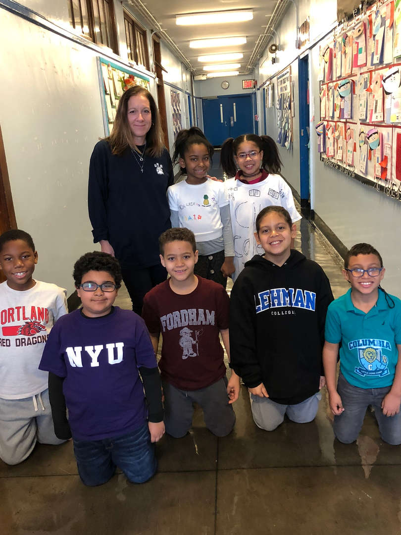 Seven students and a teacher wearing college gear.
