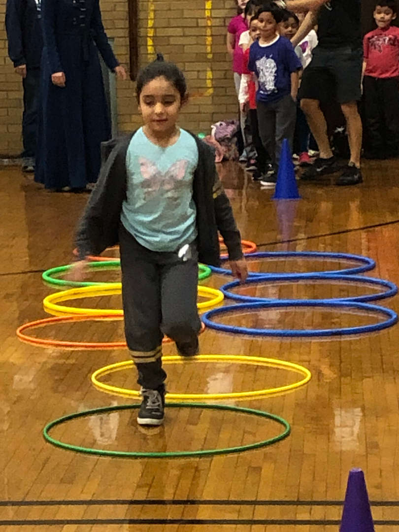 A student stepping into various hoops.