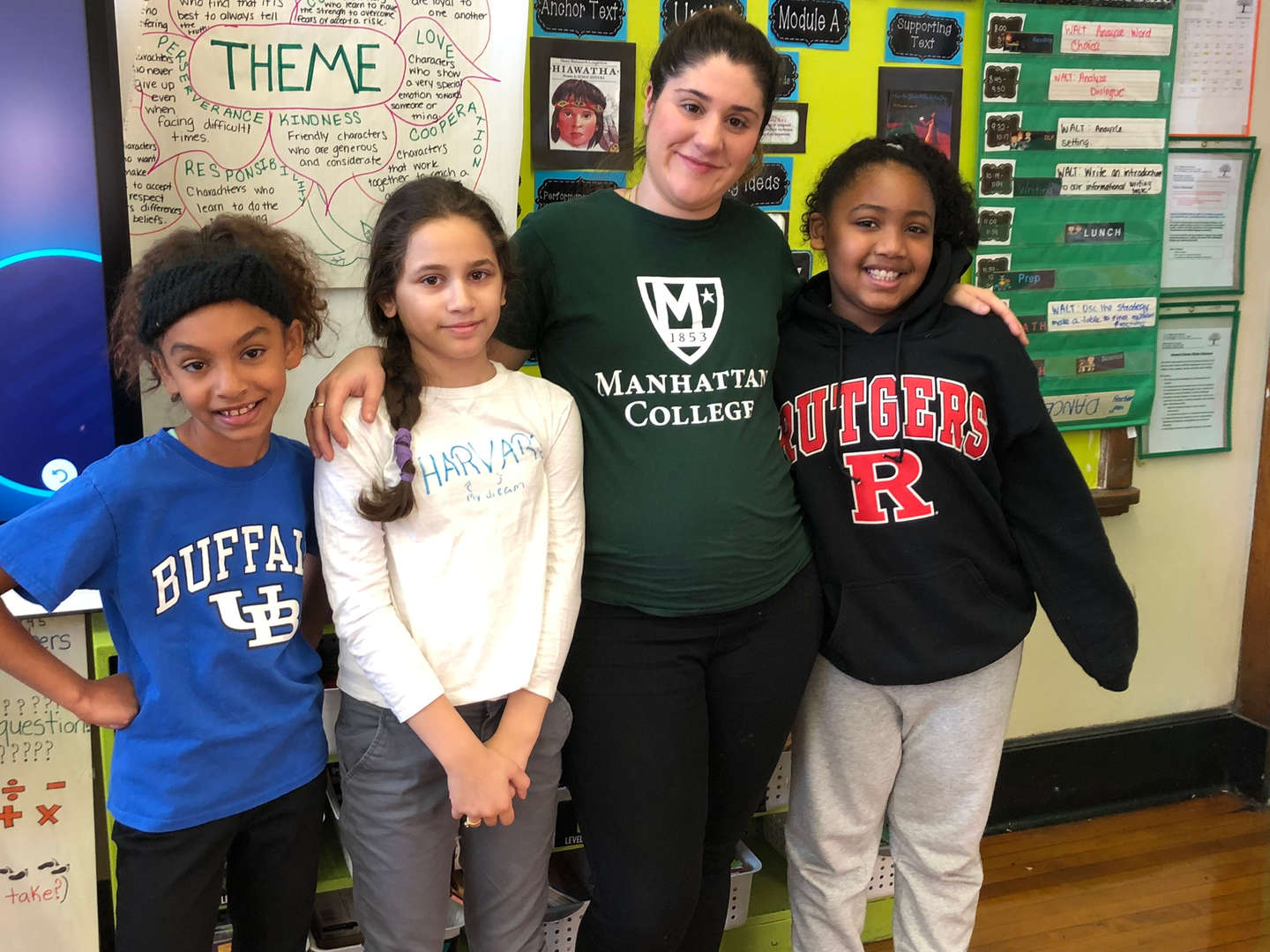 A group of 4th graders with their teacher in college gear.