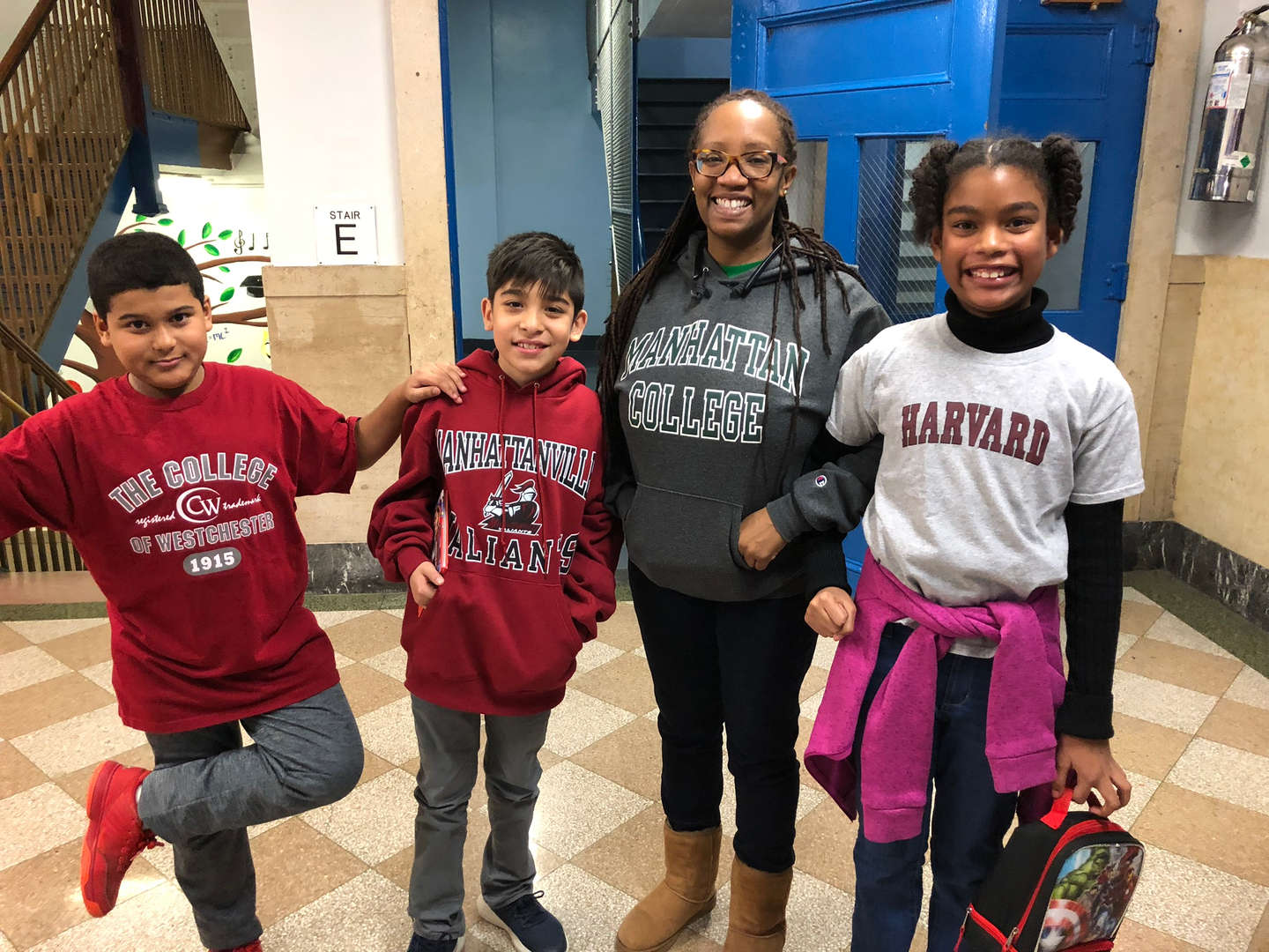 A teacher and three students in college gear.