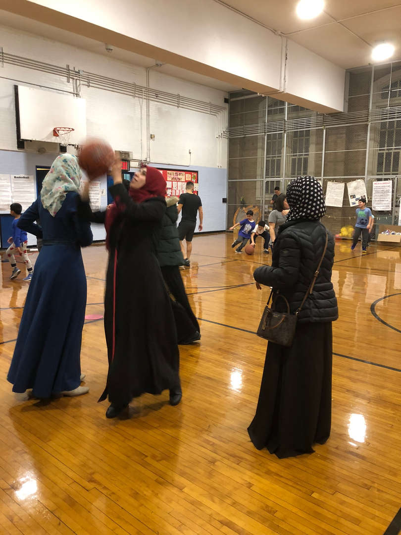 Three mothers playing basketball.