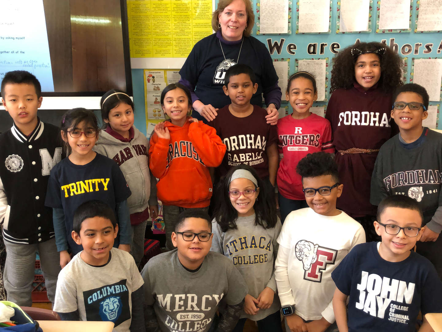 Third graders and their teacher wearing college gear in their classroom.