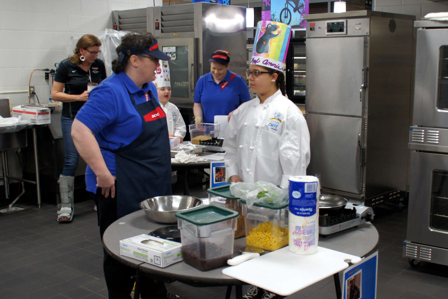 Cooking Competition student and staff helper review recipe and food items.