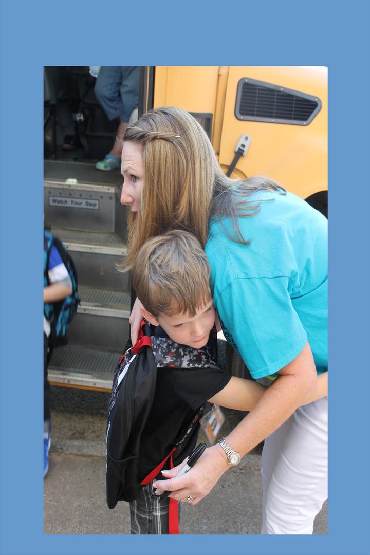 student hugs staff member