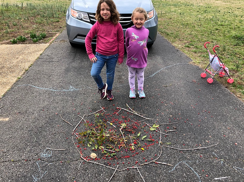 student designing art project on her driveway with little sister