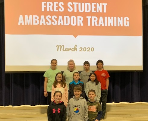 fifth grade student ambassadors receive their training and pose for picture
