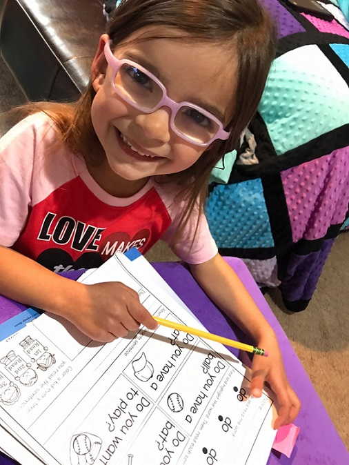 student smiling with her worksheet and pencil
