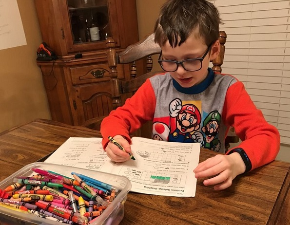 student working with crayons on a workbook