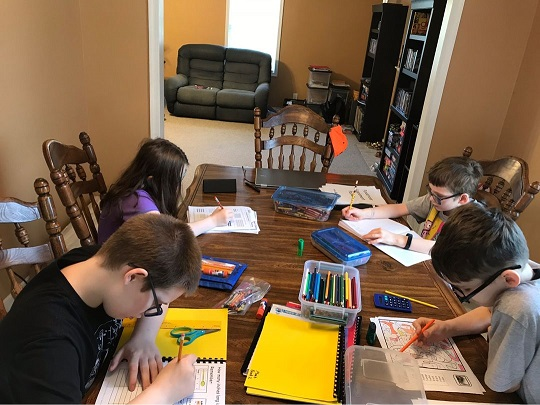 four students working at the kitchen table