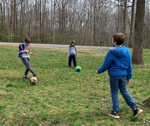 three kids playing kickball