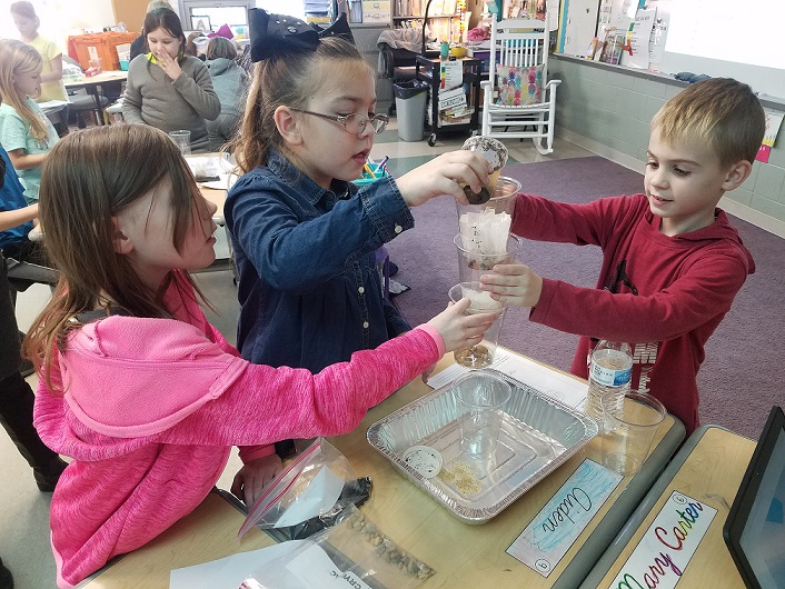 third grade students work together on a science experiment