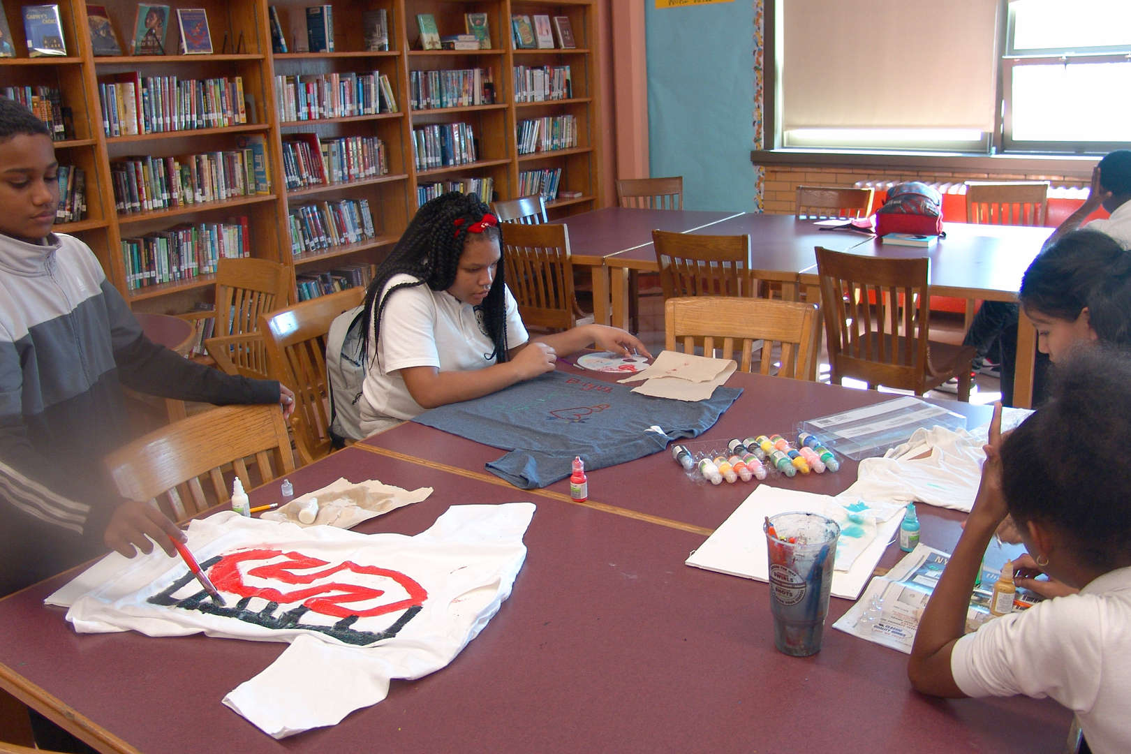 Kids working together to paint shirts