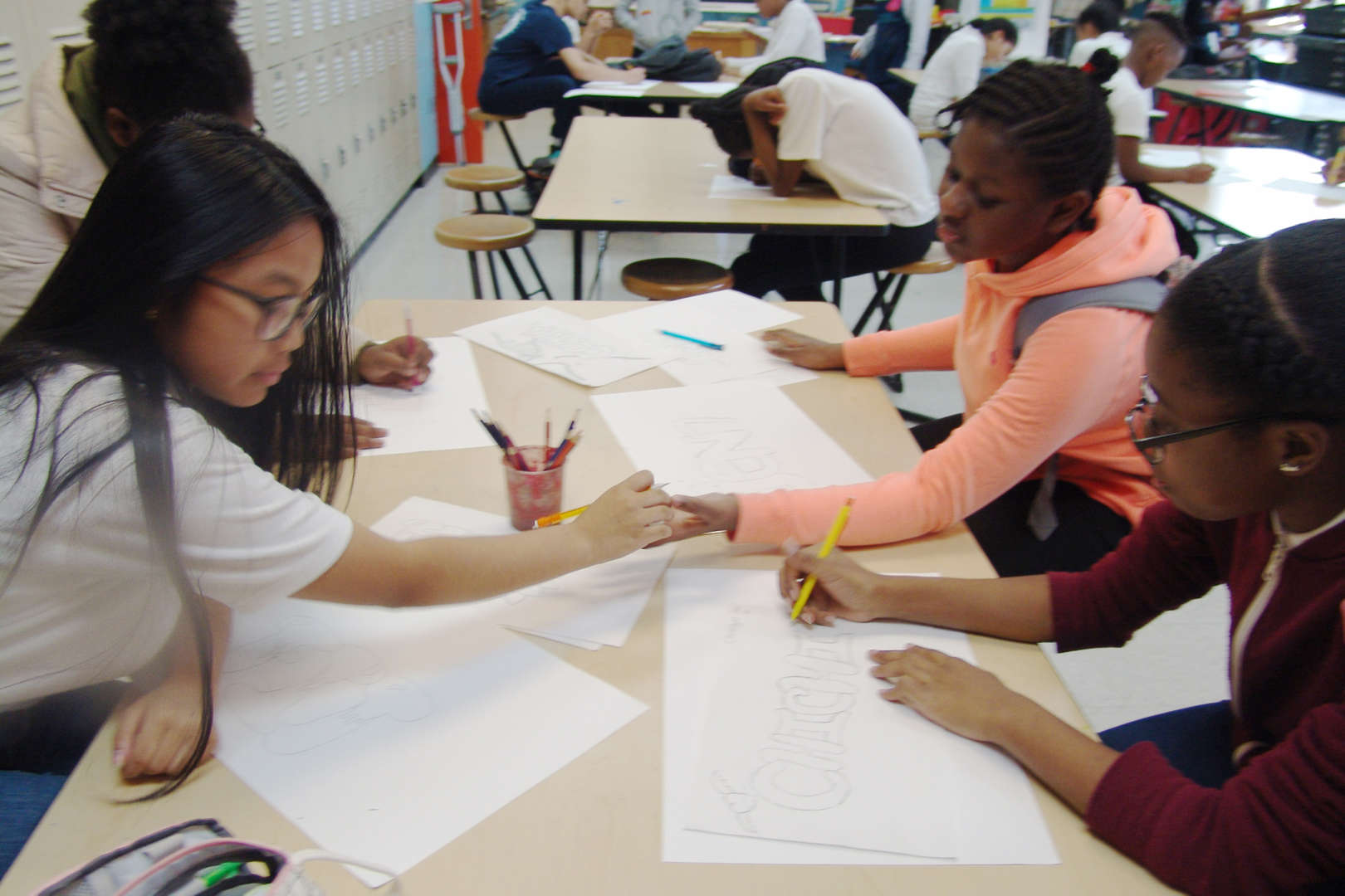 Students drawing with one another
