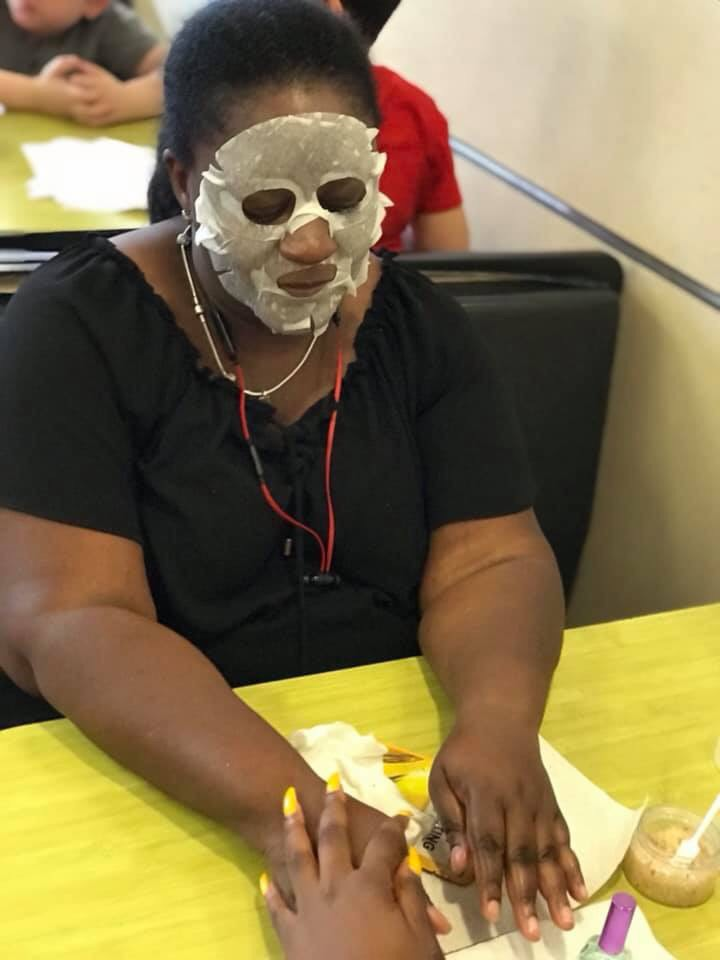 A woman wearing a face mask and getting her nails done