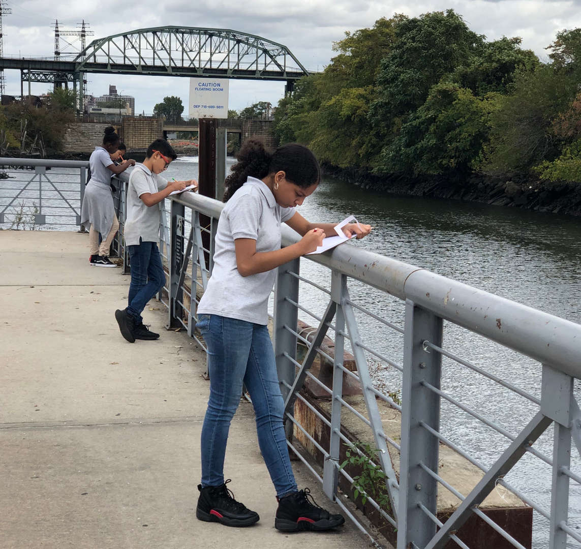 Three students lean on a railing overlooking the Bronx River while the draw what they see.