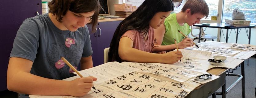 Mandarin 1 students writeChinese calligraphy using a brush and ink.