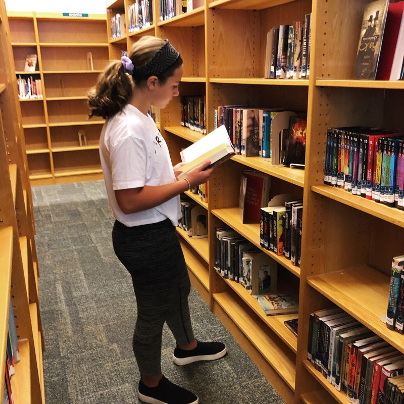 Student selecting book from library stacks.
