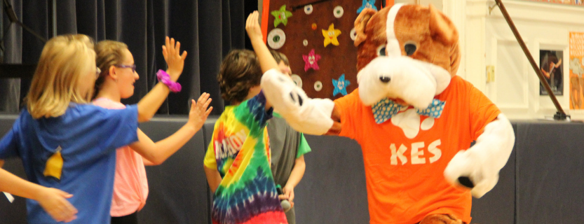 Students high-five Buddy at the October Sharing Assembly.