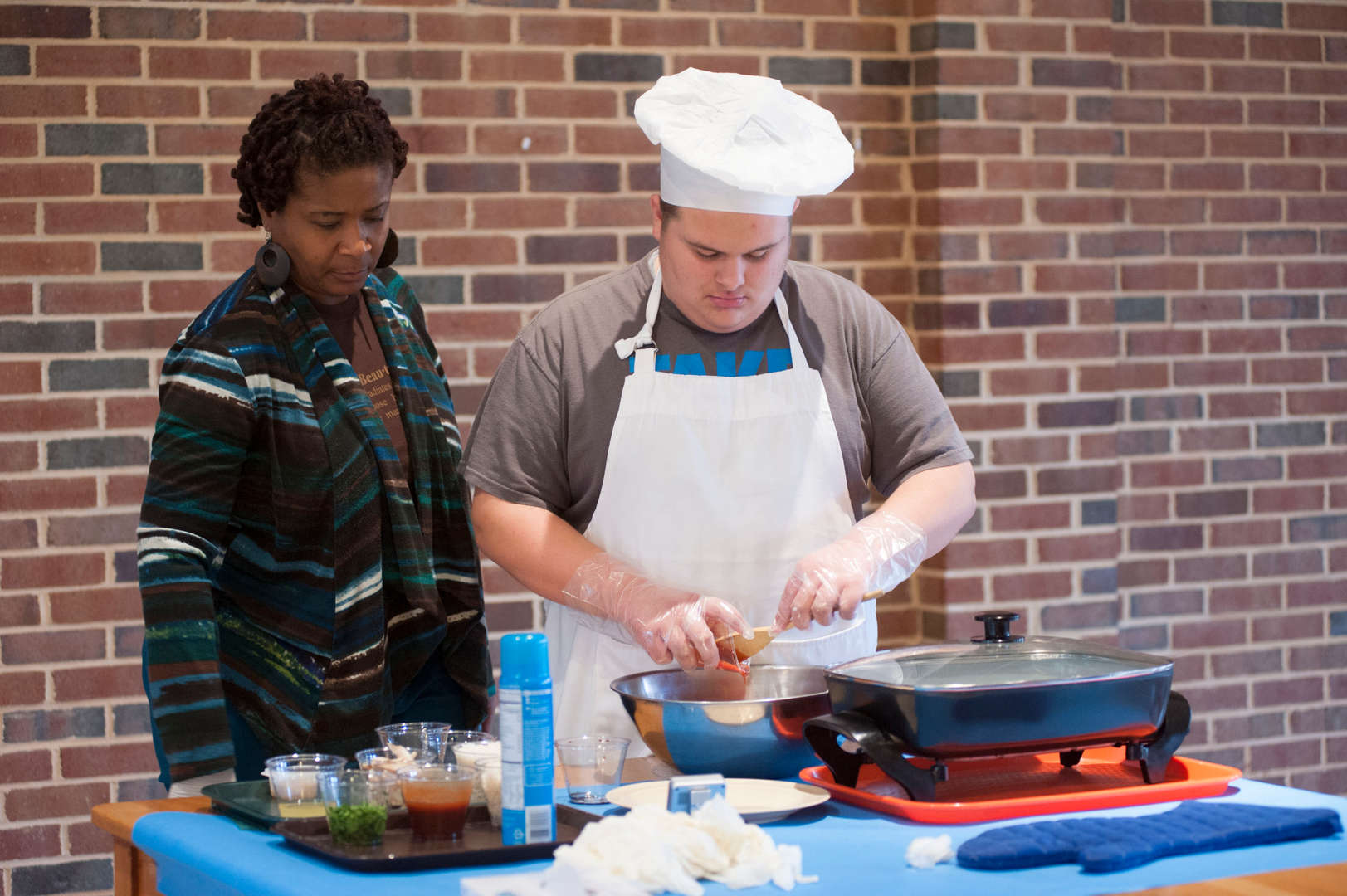Governor Morehead student demonstrates how to cook hawaiian chicken during the November 30th Celebration of Cooking with the Visually Impaired Program.