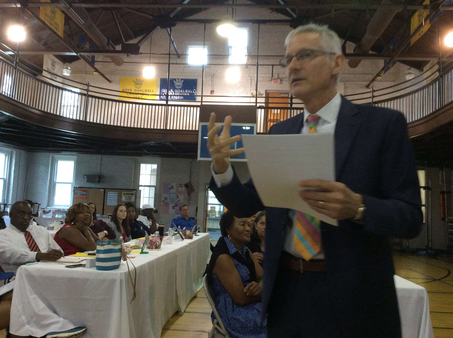 Mr. Hawting is expressing himself using hand gestures as faculty and staff look attentively.