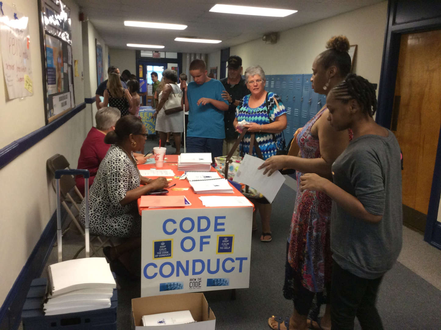 Students stop to pick up copies of the Code of Conduct before visiting other stations.